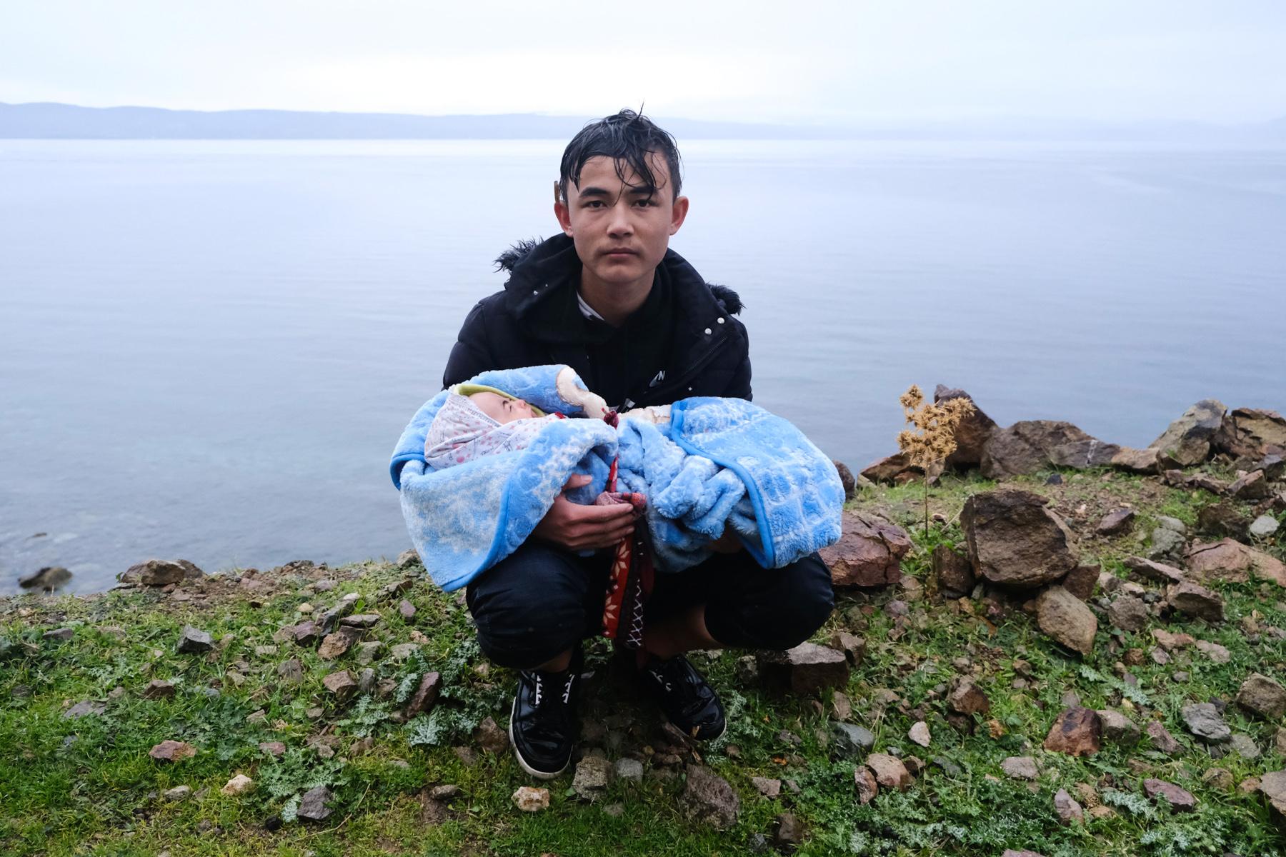 Ένας μετανάστης κρατά ένα μωρό στην άκρη του δρόμου, περπατώντας από το χωριό Σκάλα Συκαμιάς, στο νησί της Λέσβου.    Πέμπτη 5 Μαρτίου 2020.