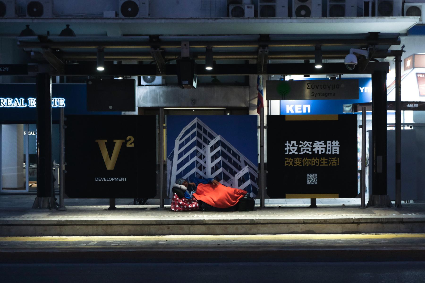 Ένας άστεγος κοιμάται σε σταθμό τραμ, μπροστά από διαφήμιση της Golden visa με στόχο Κινέζους πελάτες στην Ελλάδα.  Αθήνα, Αύγουστος του 2020.