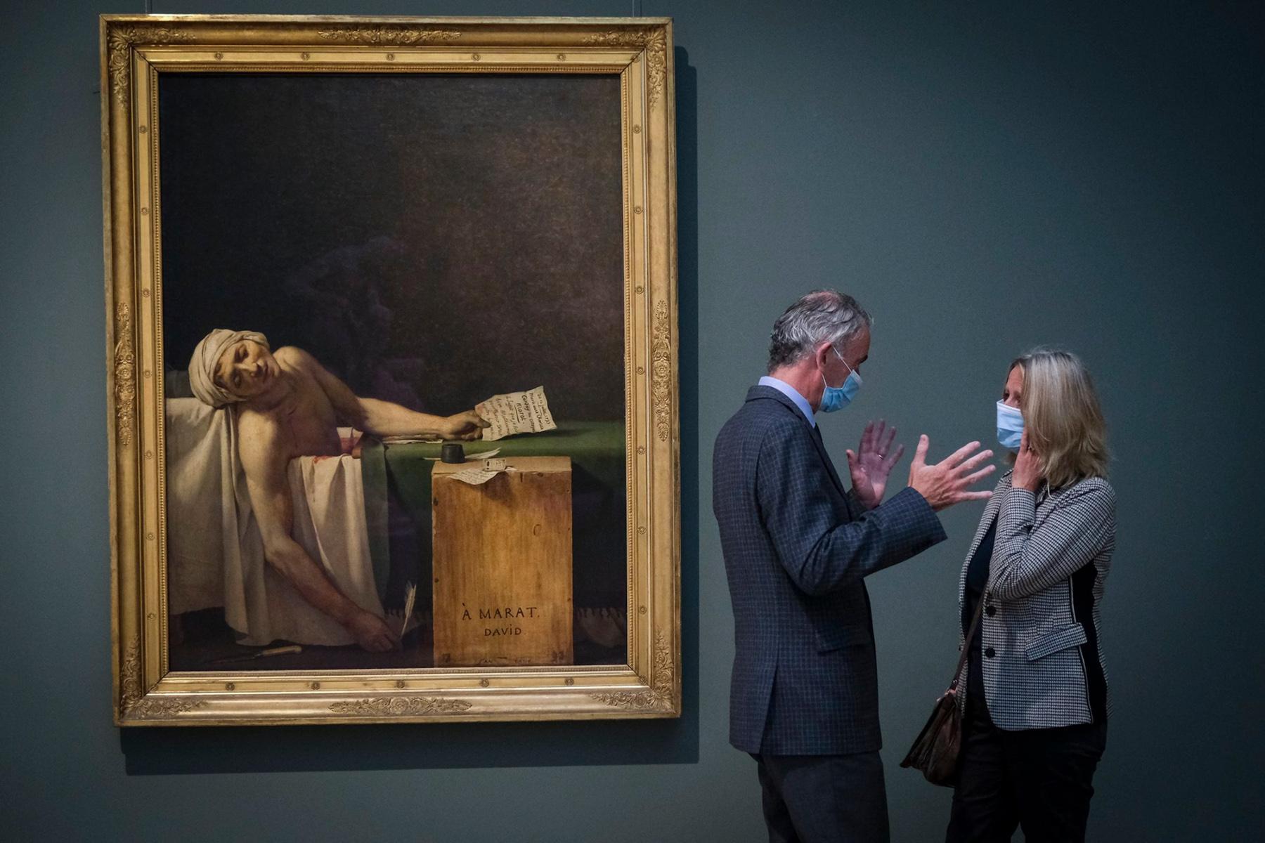 """Επισκέπτες με προστατευτικές μάσκες στέκονται δίπλα στον πίνακα του Ζακ-Λουί Νταβίντ (1793) """"Ο Θάνατος του Μαρά"""",   του δολοφονημένου Γάλλου επαναστάτη ηγέτη Jean-Paul Marat,  στο Βασιλικό Μουσείο Καλών Τεχνών στις Βρυξέλλες 19 Μαΐου 2020"""